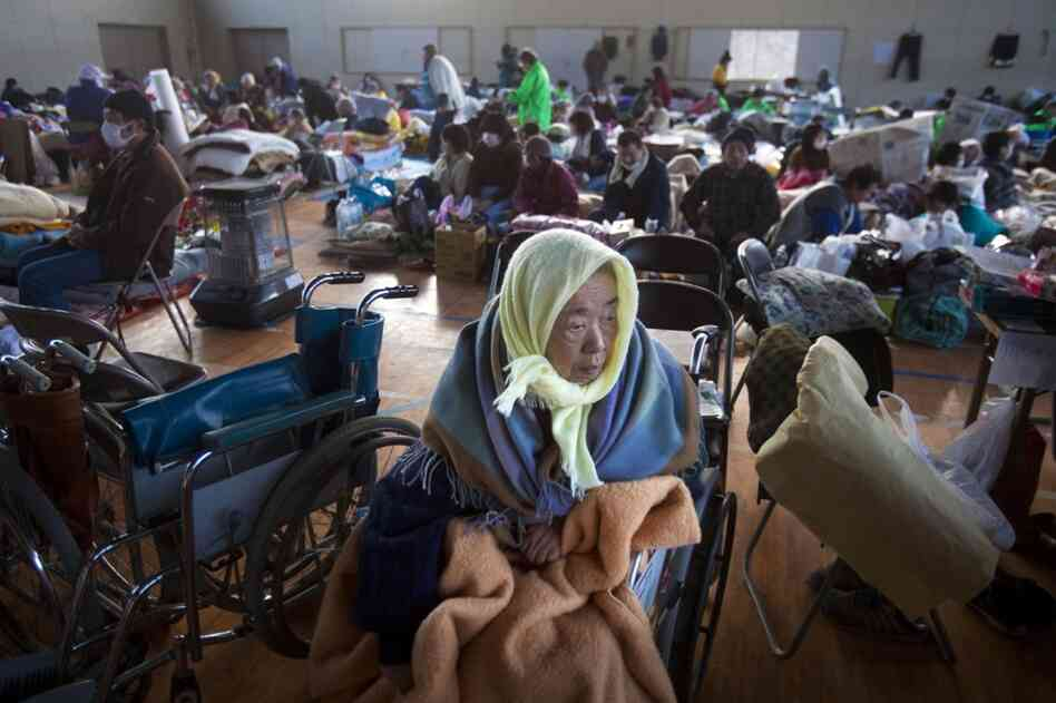 Refugees, including 53 who were saved from a retirement home, take shelter inside a school gym in the leveled city of Kesennuma, northeastern Japan.