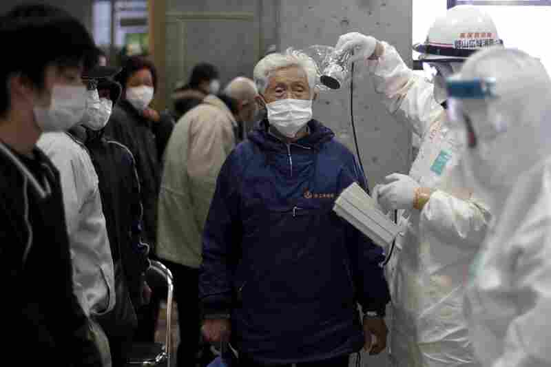 A man is scanned for radiation exposure at a temporary scanning center for residents near the Fukushima Daiichi nuclear power plant in Koriyama, Fukushima prefecture.