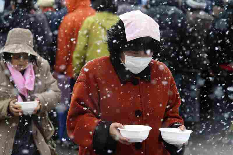 Evacuees carry food from a soup kitchen back to their makeshift shelter in Minamisanriku, northern Japan.