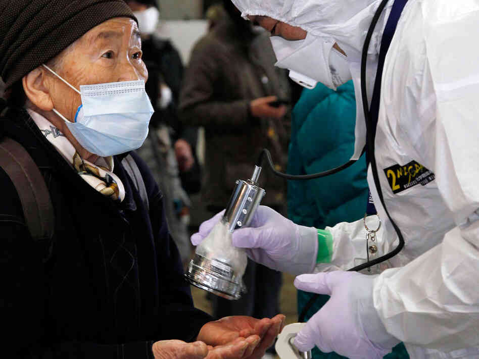 An official in a full radiation protection suit scans an evacuated elderly woman (L) with a geiger counter to check radiation levels in Koriyama city in Fukushima prefecture, about 60km west from the crisis-hit Tokyo Electric Power Co (TEPCO) Fukushima Nuclear plant, on March 16, 2011.