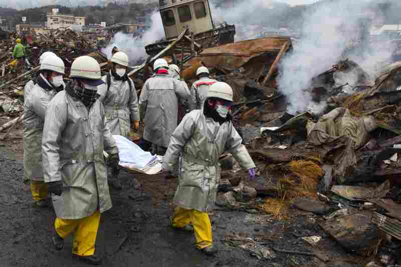 Rescue workers carry a body from the rubble of a village in Kesennuma, Miyagi province.