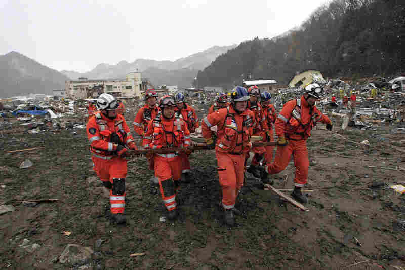 Members of a British search-and-rescue team carry a body removed from a destroyed house in Kamaishi, Japan. The official death toll climbed above 5,300 on Thursday.