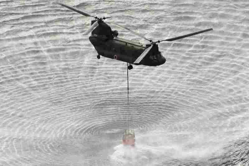 A military helicopter scoops water off Japan's northeast coast on its way to the Fukushima Dai-ichi nuclear power plant on Thursday, in an effort to cool overheated fuel rods inside the core.