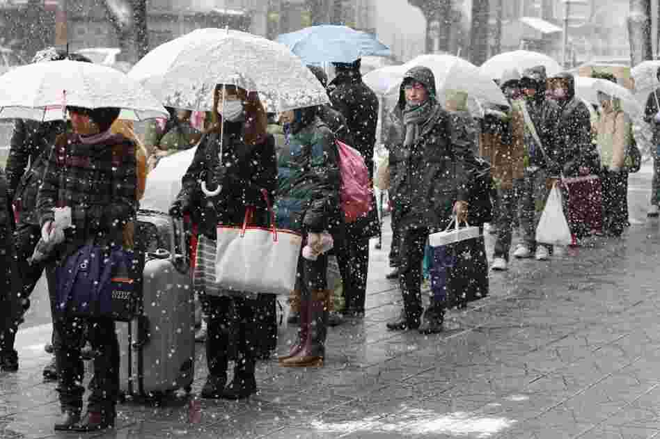 People wait in the snow for a bus to leave town in Sendai, Japan.