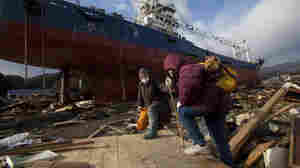 Two elderly Japanese women pass a ship that washed into their neighborhood in the leveled city of Kesennuma, in northeastern Japan, on March 17.