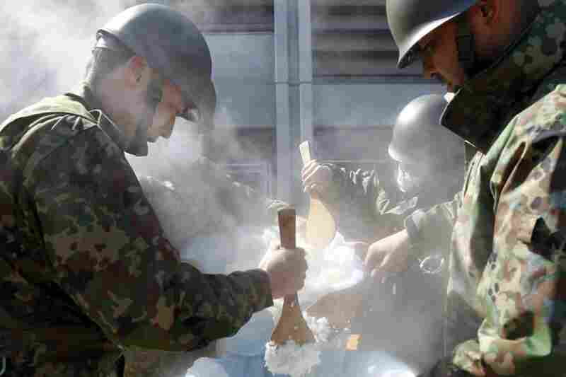 Japanese soldiers cook steamed rice to distribute to evacuees in Koriyama, Fukushima prefecture.