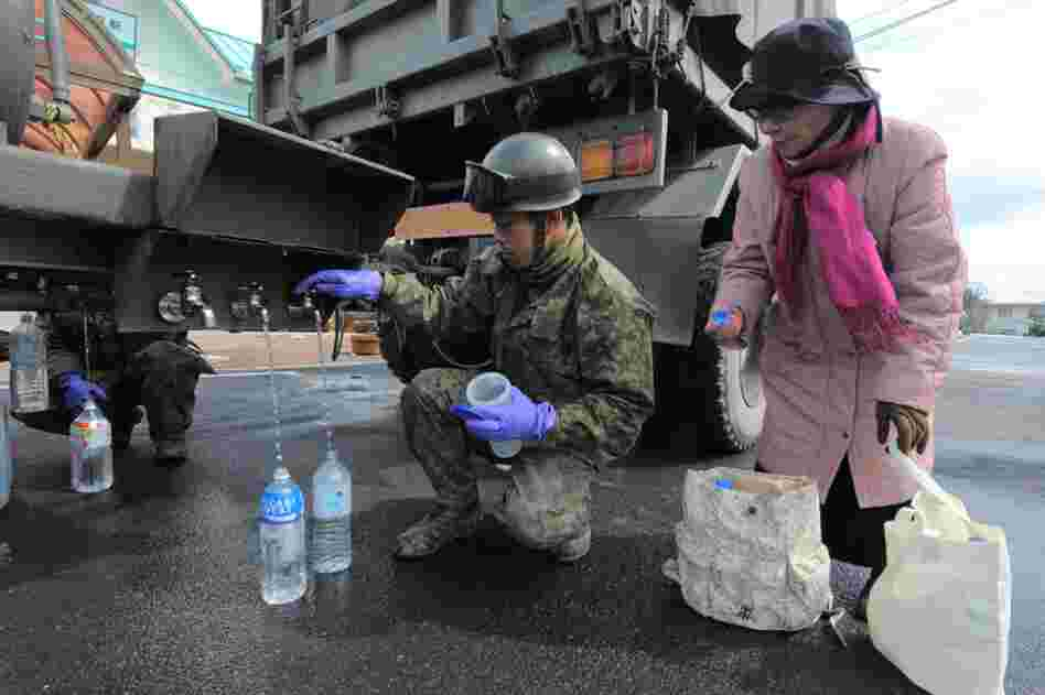 A Japanese soldier provides water for local residents in Kesennuma, Miyagi prefecture.