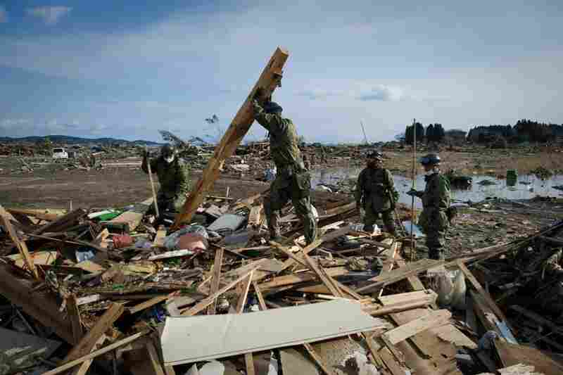 Japanese soldiers comb through the rubble of a destroyed building in the city of Kesennuma, Miyagi prefecture.