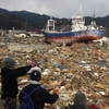 Survivors overlook the earthquake and tsunami-hit area in Kesennuma, Miyagi prefecture, Japan, on Thursday.