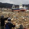 Survivors overlook the earthquake and tsunami-hit area in Kesennuma, Miyagi prefecture, Japan, on Thursday.