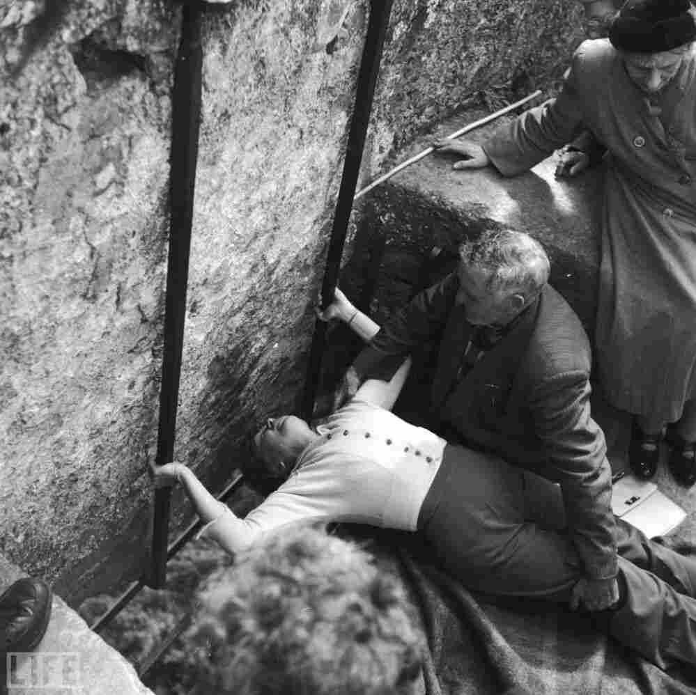 """With the help of the """"curator of the stone,"""" a woman kisses the Blarney Stone at Blarney Castle in County Cork, 1950."""