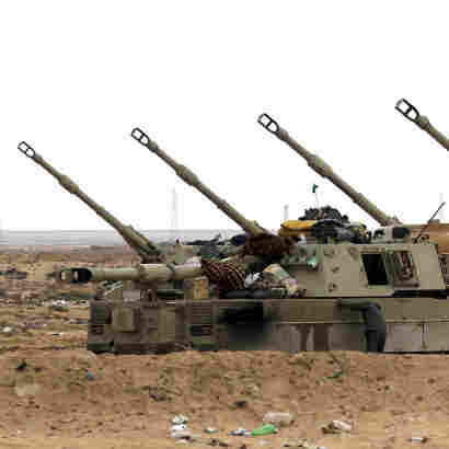 Libyan soldiers loyal to Moammar Gadhafi man artillery cannons at the western entrance of the city of Ajdabiya on Wednesday.