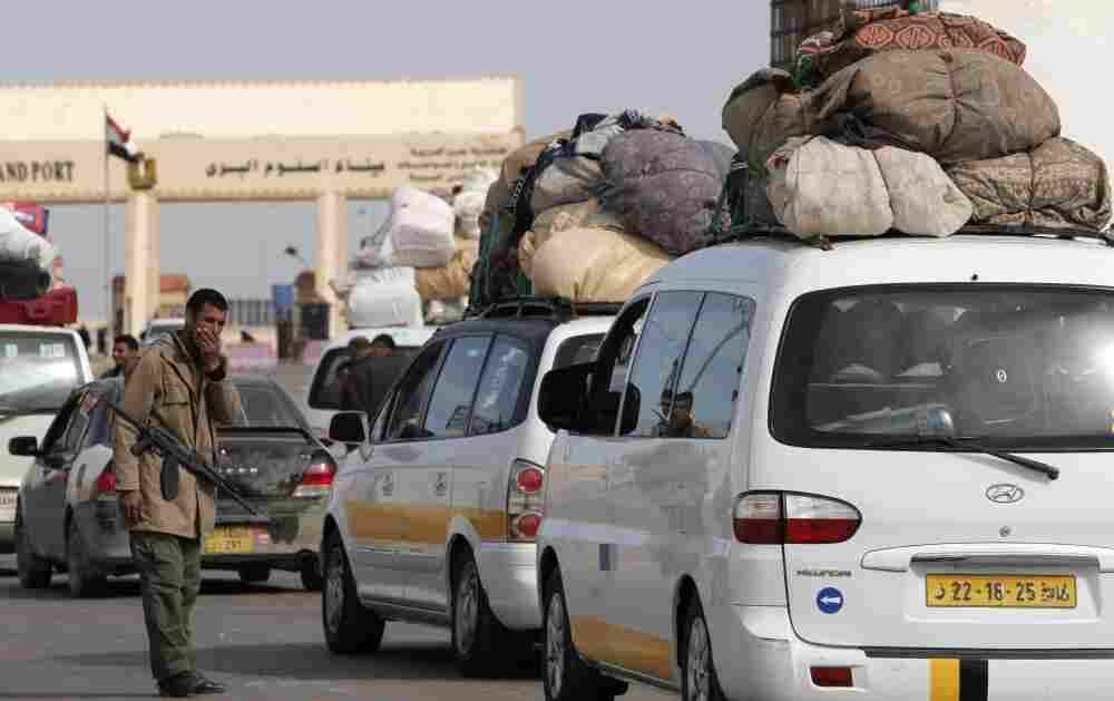 A Libyan rebel checks vehicles crossing toward  Egypt at the Libyan terminal of the Egyptian Libyan border crossing near  the border town of Musaed.