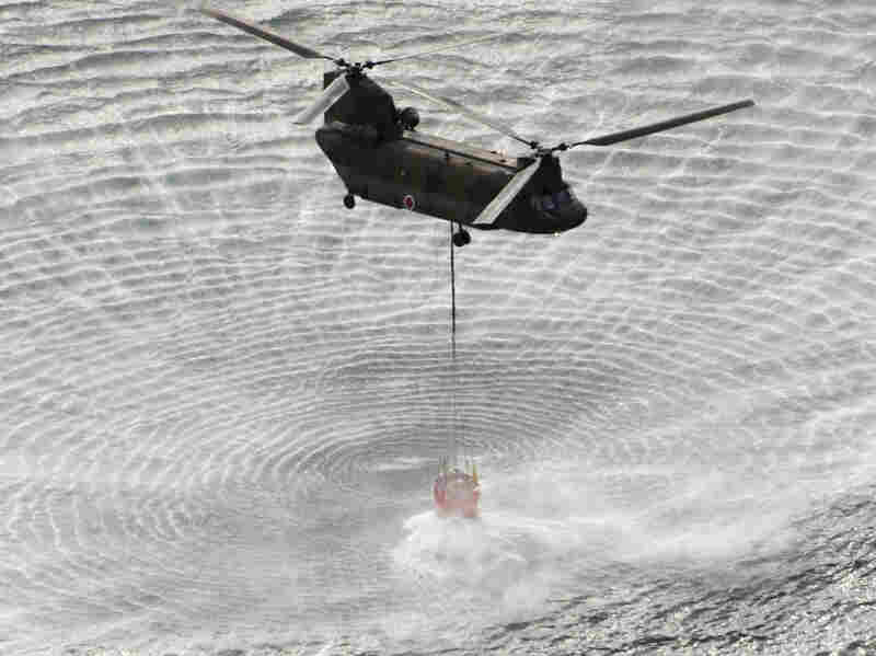 A Self-Defense Forces helicopter scoops water off Japan's northeast coast on the  way to the Fukushima Dai-ichi nuclear power plant Thursday morning. Helicopters  are dumping water on a stricken reactor to cool overheated fuel rods inside the  core.