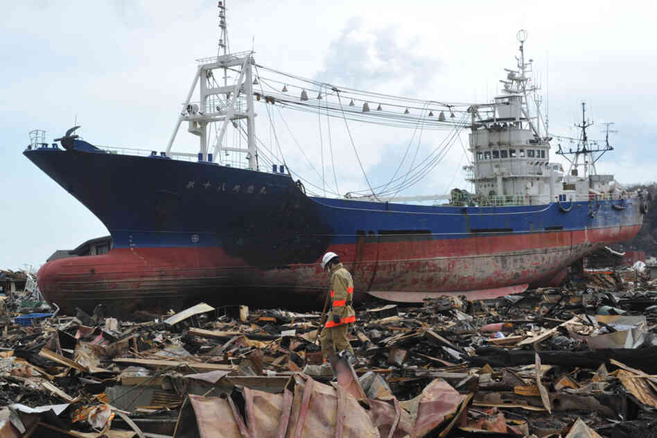 Japanese rescuers search through debris in front of a large ship washed ashore in Kesennuma, Miyagi prefecture.