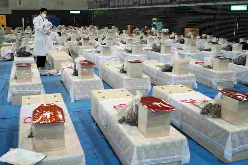 Dozens of coffins line a hall in Rifu, Miyagi prefecture. The official number of dead and missing has topped 16,600.