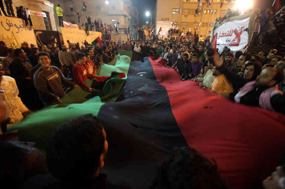 Libyans celebrate in Benghazi on Friday, one day after the U.N. approved a resolution to impose a no-fly zone over Libya. Deputy Foreign Minister Khaled Kaim said in Tripoli that Libya is ready for a cease-fire with the rebels battling leader Moammar Gadhafi, but wants to discuss in advance how it would be implemented.