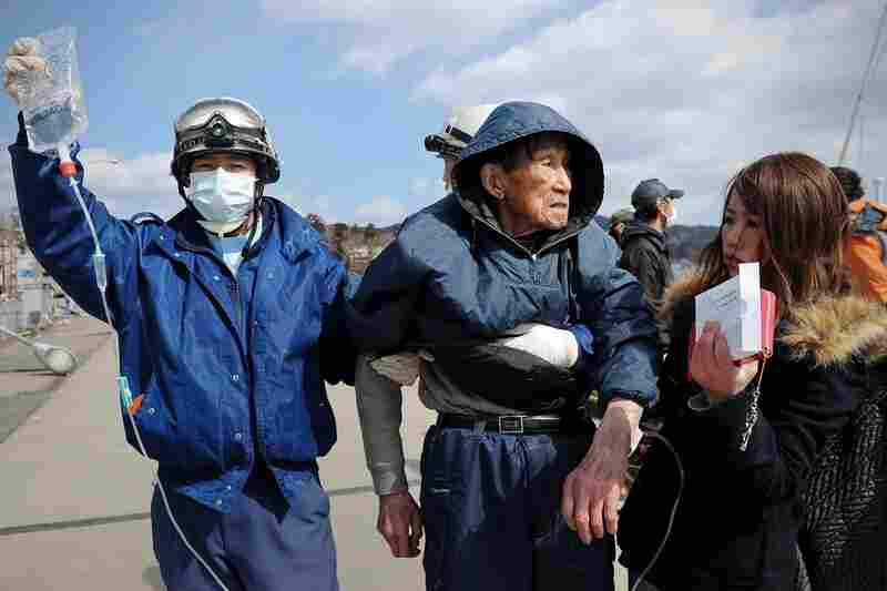A Japanese rescue worker transports an elderly survivor to a hospital in Kesennuma.