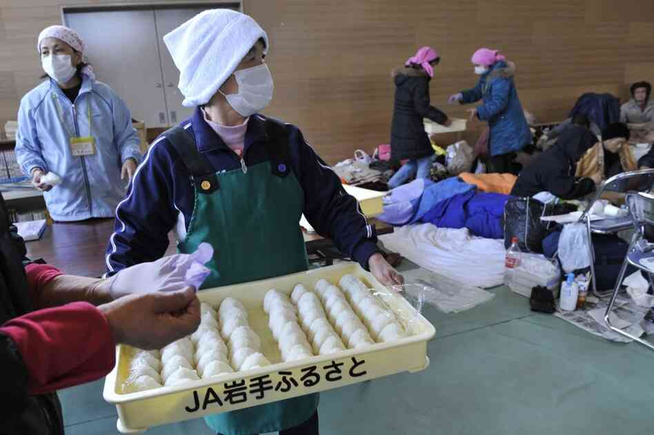 Volunteers distribute rice balls at a shelter in Rikuzentakata, Iwate prefecture.
