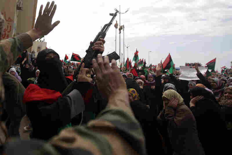 "A Libyan woman fires a weapon into the air as people gather to celebrate in the eastern rebel-held city of Benghazi on Friday, as U.N. Secretary-General Ban Ki-moon warned the Libyan regime that anyone responsible for attacks on unarmed civilians will be ""brought to justice."""