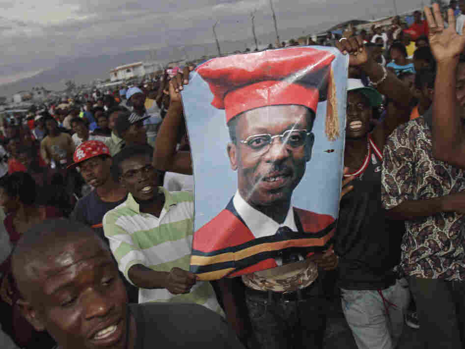 Supporters of Haiti's ousted President Jean-Bertrand Aristide hold up a poster of the exiled leader in Port-au-Prince, Haiti, Thursday March 17, 2011.