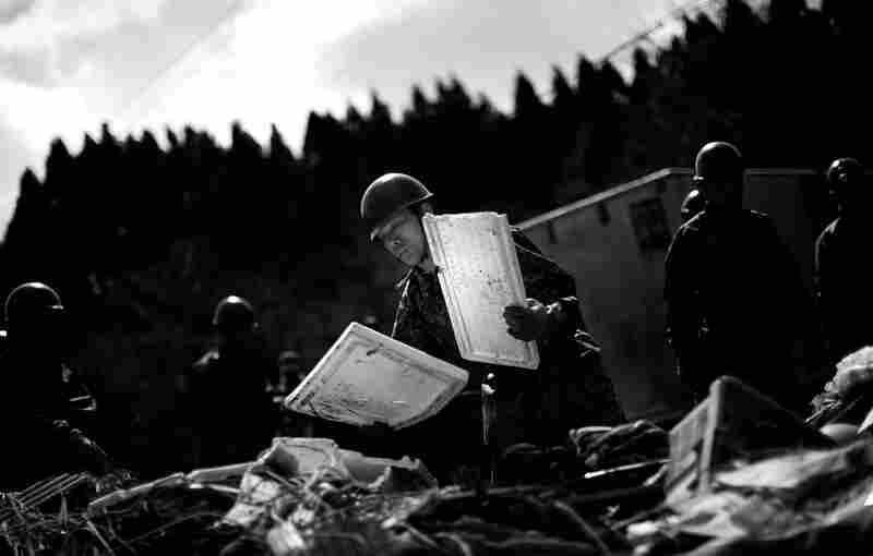 Japanese Self-Defense Force soldiers help remove the remains of a fishing market near Noda.