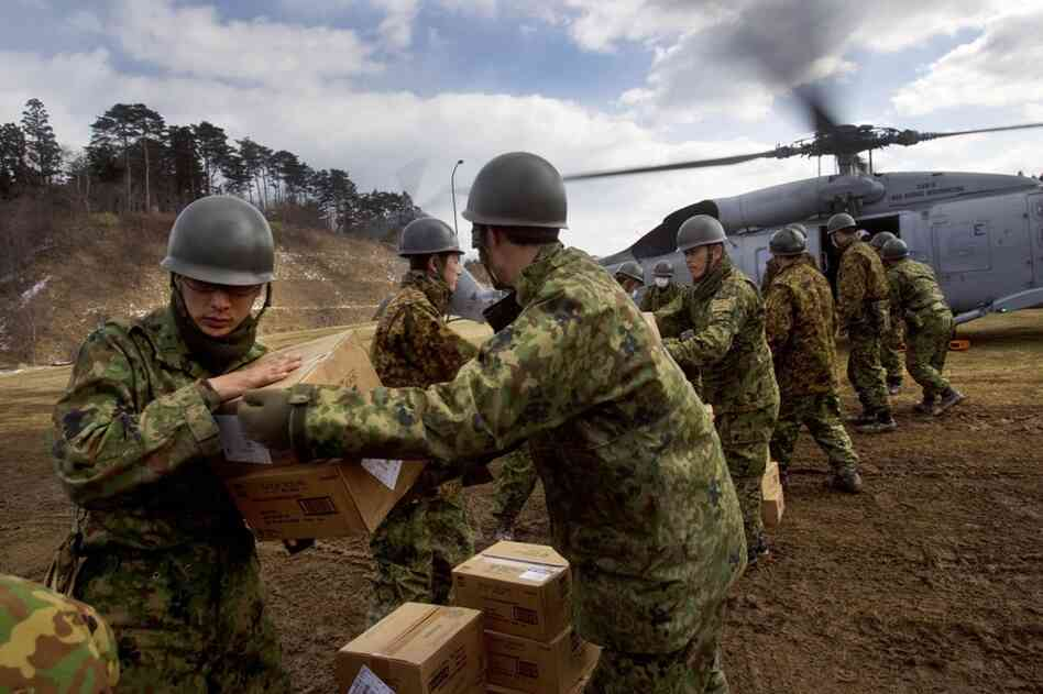 Japanese troops unload food aid from a U.S. helicopter in Minamisanriku.