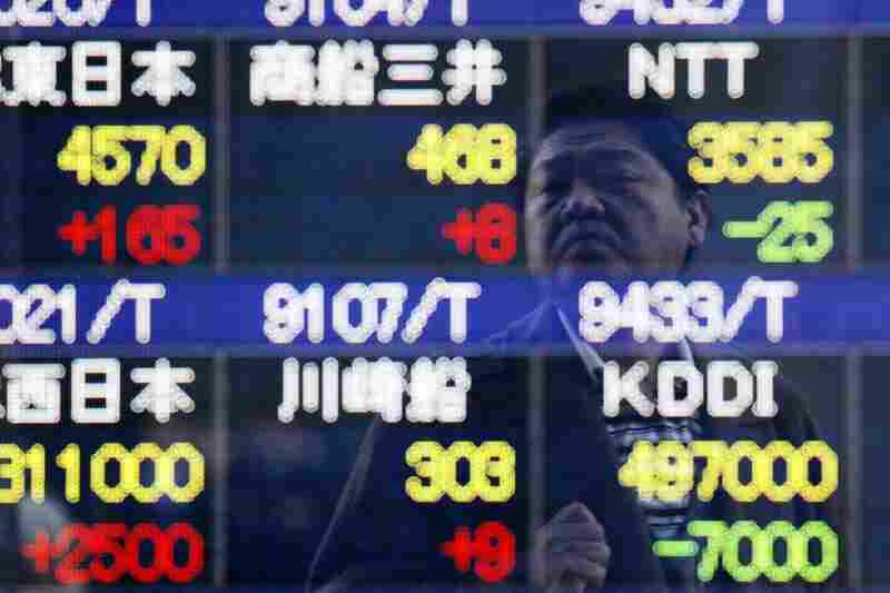 A man looks at the stock price board in Tokyo. Japan's stocks posted solid gains Friday, and the yen relaxed after hitting historic highs, after the world's seven major industrial nations agreed to intervene in currency markets to help the earthquake-stricken nation.