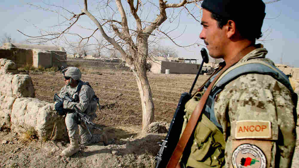 An Afghan police officer (right) stands near a U.S. soldier in the Panjwai district of Kandahar province, Afghanistan, on Dec. 8.