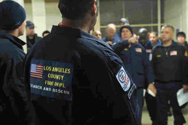 Members of search and rescue teams from Los Angeles County and Fairfax County, Va., get a briefing Monday before heading to Japan to help with rescue and recovery efforts.