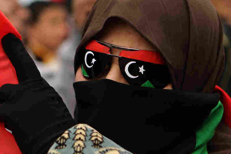 A Libyan woman with glasses bearing the flag of the former Libyan monarchy joins thousands celebrating in the rebel-held eastern city of Benghazi on Friday after a U.N. vote approved a no-fly zone.