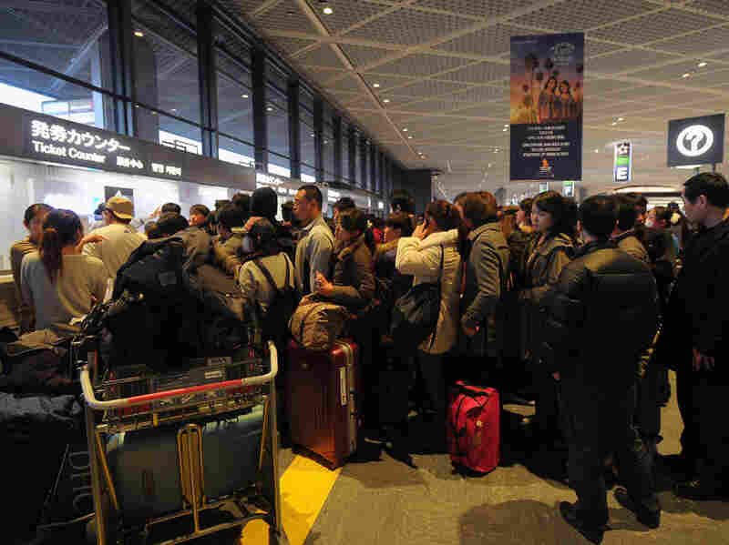 People line up to buy tickets for the earliest possible flight Friday at Narita International Airport.