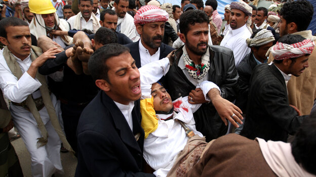 Yemeni anti-government protesters carried away a wounded demonstrator in Sanaa earlier today (March 18, 2011).