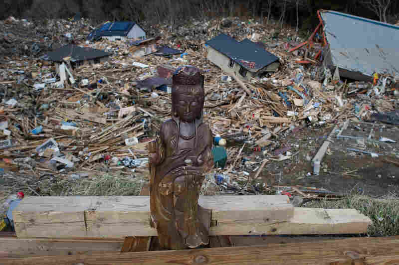A religious statue placed by local residents stands among the rubble in Kesennuma.
