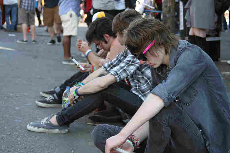 Showgoers resting on a curb in between sets.