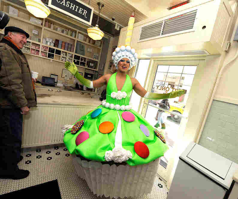 "...and Magnolia Bakery created a pistacio cupcake with a meringue topper (inspired by Lizzie and Tim's costume) as the ""official cupcake"" of Priscilla Queen Of the Desert. Actor Thom Allison attended the unveiling, in full cupcake getup, in the New York bakery's shop."