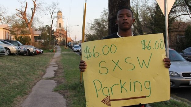 Austinite D'wazauhn Washington working a make-shift pay-to-park lot in East Austin on Friday.