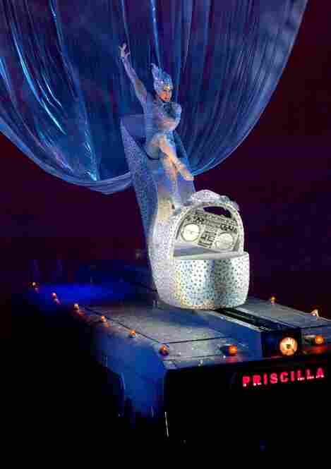"Nick Adams, as Felicia, sits atop a six foot tall high heel on the roof of the Priscilla in the finished bodysuit for the ""Bus Top Aria"" song. Like the bodysuit, the shoe is fully covered in Swarovski crystals. (Photo by Joan Marcus)."