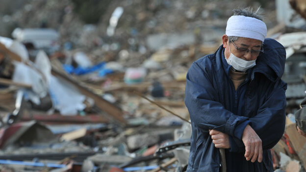 Surrounded by debris in the devastated city of Rikuzen-Takada, Japan, a man rested on his walking stick earlier today (March 19, 2011).