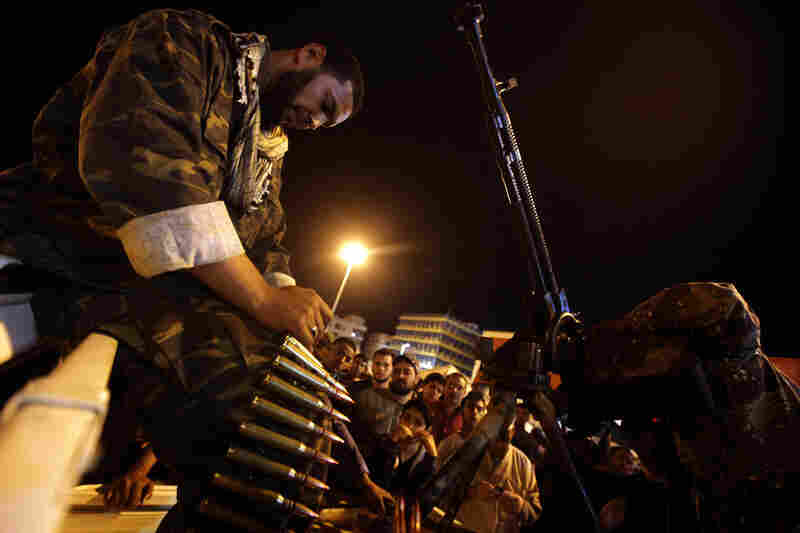 A Libyan rebel loads ammunition in the center of Benghazi on Thursday. The city's rebel commanders ordered fighters to man artillery posts and missile batteries after Gadhafi announced an imminent assault on the city.