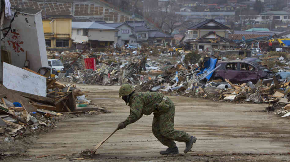 The Japanese military works to clear roads in Ofunato, Japan on Sunday so that it can bring in more cranes and bulldozers to aid recovery operations.