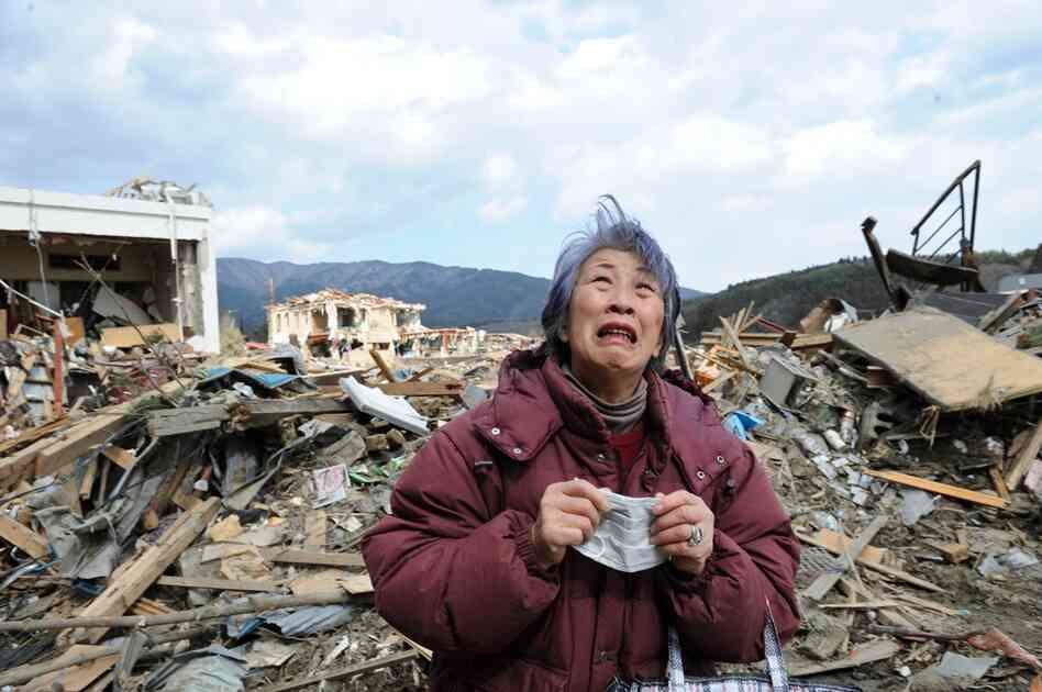 A woman cries amid the rubble in Rikuzentakata.