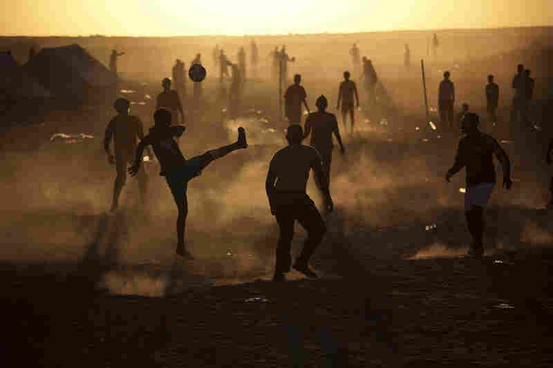 Migrant workers who fled the unrest in Libya play football at a refugee camp on the Tunisia-Libyan border on Thursday. More than 250,000 migrant workers have left Libya for neighboring countries, primarily Tunisia and Egypt, in the past three weeks.