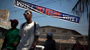 A banner in Haiti's Cite Soleil neighborhood encourages residents to vote Sunday in the second round of elections.