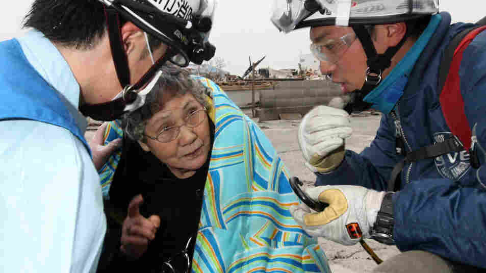 Eighty-year-old Sumi Abe is wrapped in a blanket after being rescued from the wreckage of her home in the city of Ishinomaki in Miyagi prefecture on Sunday. Abe and her grandson Jin Abe were in the kitchen when the quake struck on March 11.