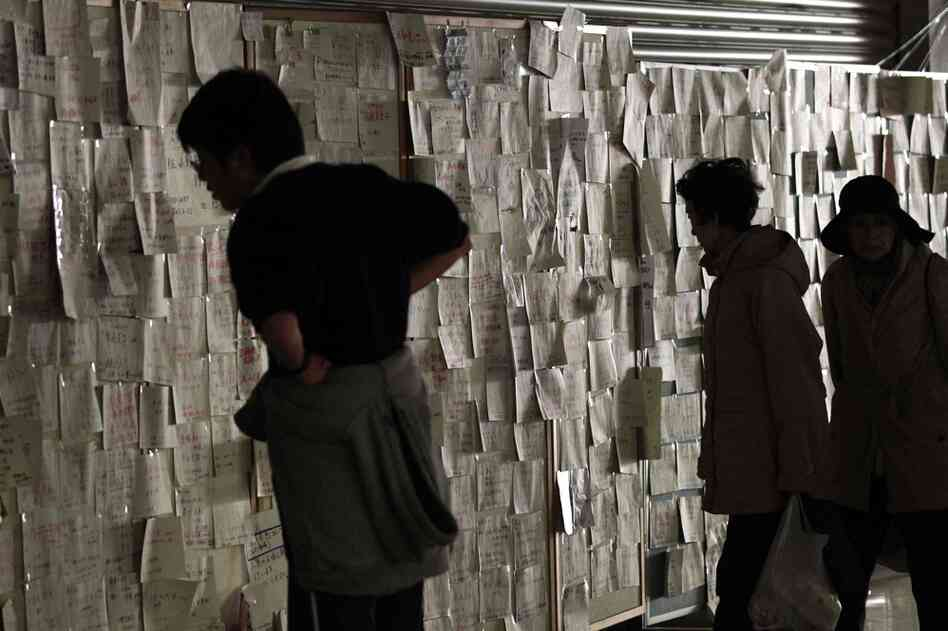 Messages of the whereabouts of people who survived the tsunami cover the walls of the city hall in Kesennuma, Miyagi prefecture.