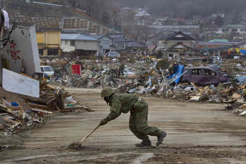 A member of the Japanese military clears a road to allow cranes and bulldozers into Ofunato.