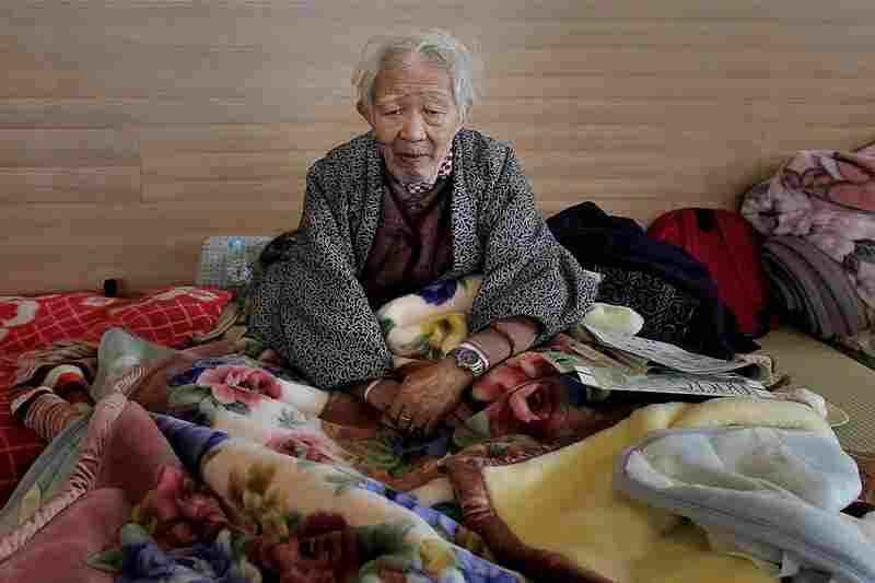 A man sits in an evacuation center in Rikuzentakata.