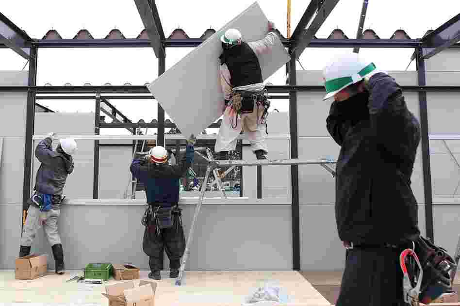 Construction workers build temporary housing in Rikuzentakata.