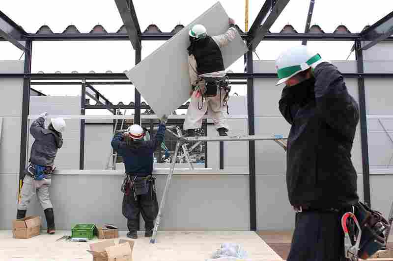 Construction workers build temporary housing in Rikuzentakata.